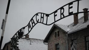 Vstupní brána do koncentračního tábora Auschwitz s cynickým nápisem Arbeit macht frei, tedy Práce osvobozuje