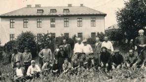 Řečtí uprchlíci před budovou kasáren v Těchoníně v roce 1957. Od roku 1962 slouží opět vojenským účelům, v současnosti v nich sídlí Odbor biologické ochrany Armády ČR, jehož součástí je specializovaná infekční nemocnice. Foto: Paměť národa