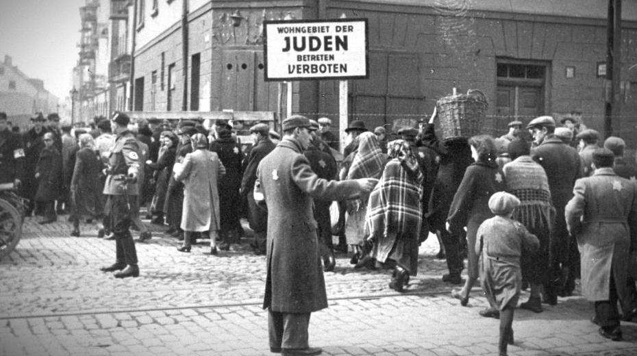 Židovský policista a německý voják usměrňují provoz na hlavní ulici, která rozdělovala ghetto. Později byl na této křižovatce postaven dřevěný most. U vchodu do ghetta je v němčině Židovská obytná oblast, vstup zakázán. Foto USHMM/Wikimedia Commons