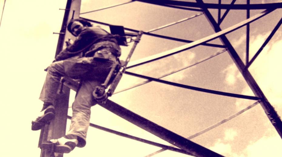 Robert Ospald stoupá na sloup vysokého napětí se speciálním vozíkem. Foto: Paměť národa