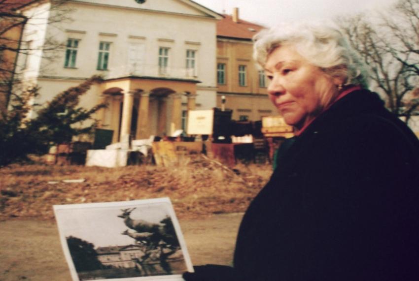 Helena Vovsová u dolního zámku v Panenských Břežanech s fotografií soch jelenů odstraněné Linou Heydrichovou. Zdroj: Paměť národa