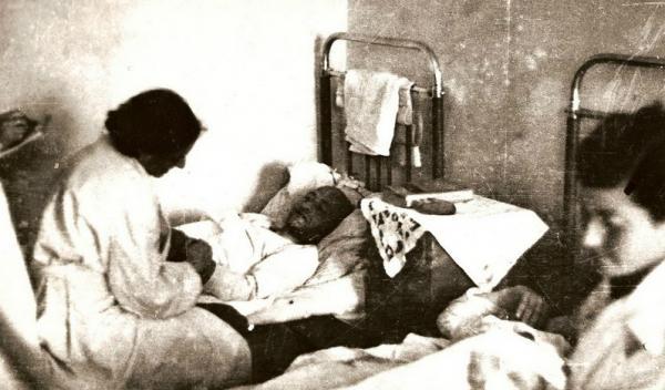 Dr. G. Englová v polní nemocnici na vizitě u pacienta, vpravo zdrav. sestra Žofie Scheimannová v roce 1944.