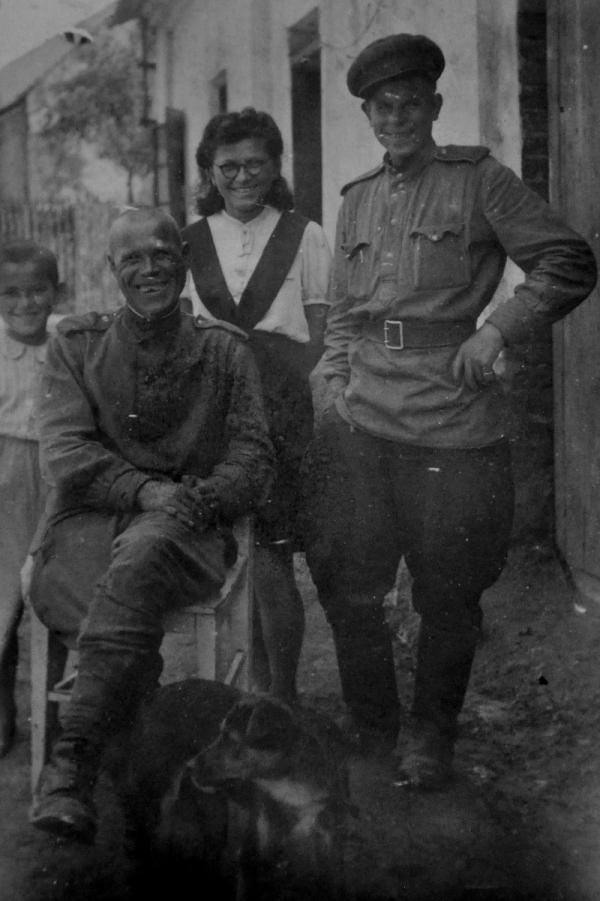 Irena Ondruchová, bratranec Luboš Adámek a pes Alík s ruskými vojáky ve Výškovicích v květnu 1945. Foto: Paměť národa