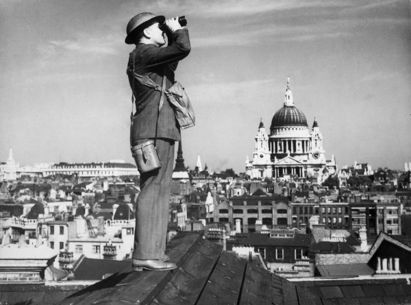 Jeden z dobrovolných pozorovatelů na londýnské střeše během bitvy o Británii. V pozadí kupole katedrály sv. Pavla, která jako zázrakem zůstala netknutá, ačkoli Luftwaffe Londýn zasypávala zápalnými bombami každou noc.