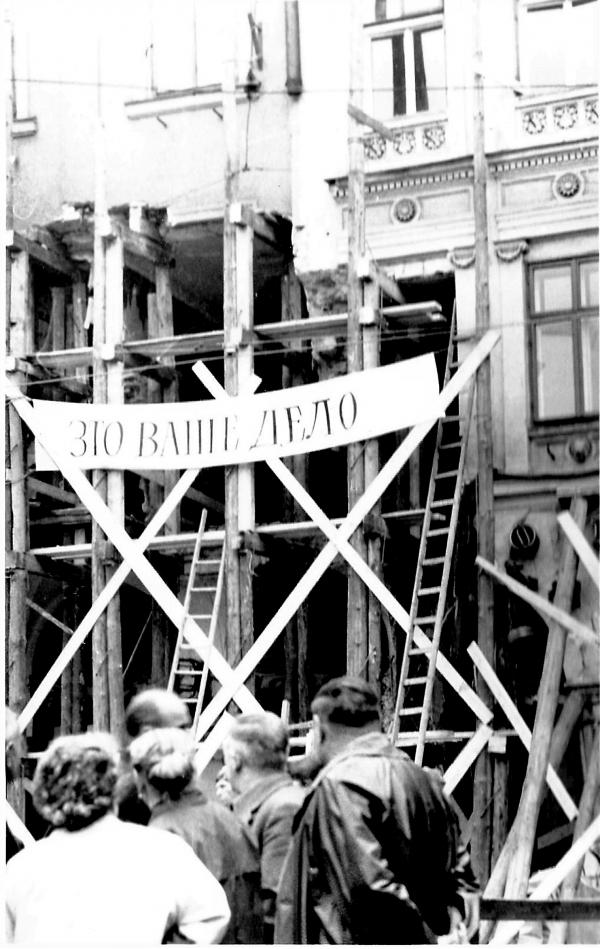 Podloubí zničené nárazem sovětského tanku s transparentem v ruštině - To je vaše práce