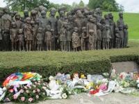 Pohled na bronzové sousoší lidických dětí v Lidicích. Před pomníkem jsou květiny a hračky