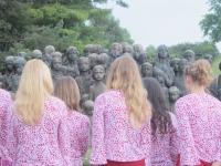 Dívky z pěveckého sboru před sousoším lidických dětí (r. 2015)