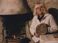 """Marie Uchytilová s jednokorunovou československou mincí, na kterou r. 1956 vyhrála veřejnou soutěž; sama autorka o práci prohlásila: """"…jaká to příležitost pro umělce – své srdce celému národu položit do dlaně!"""""""