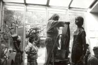 Marie Uchytilová na štaflích zakrývá mokrým hadrem sochu velké dívky z hlíny (r. 1988)