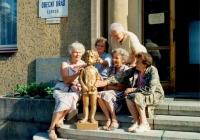Lidické maminky hladí sochu lidického dítěte před obecním úřadem v Lidicích (r. 1992)