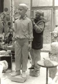 Marie Uchytilová na kostce retušuje sochu chlapce, poslední sochu sousoší lidických dětí (březen 1989)