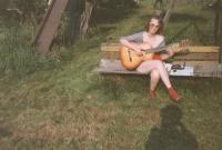 Sedmnáctiletá Iveta poctivě cvičí na zahradě na kytaru.