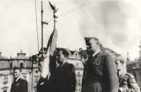 """Slavnostní leteckou standartu drží zbrojíř 311. československé bombardovací perutě Viktor Kropš. (Jeho osud by rovněž vydal na knihu zejména svými dramaty po roce 1948. Jeho letka byla v roce 1946 převelena na letiště Plzeň-Bory. Při přehlídce uskutečněné právě v Plzni v roce 1945 se seznámil se svou budoucí chotí Jiřinou. Po únoru 1948 se spolu s ní za pomoci převaděče pokusili jedné noci projít domažlickými lesy za hranice, avšak byli zadrženi. Viktor i Jiřina se na pohraničníky vrhli, strhla se rvačka a Viktor chtěl použít i svůj revolver. Nicméně pohraničníci byli v přesile. Jiřina skončila na rok v ženské káznici a Viktor po dlouhém věznění s trýznivými výslechy nakonec v jáchymovských dolech, což mu natrvalo podlomilo zdraví. I této rodině se Jan v nejtěžších dobách snažil pomáhat a přátelské vazby se upevnily až do """"rodinného"""" pouta. Když Viktor po propuštění po několika málo letech na svobodě na následky věznění zemřel, byl Jan požádán, aby vyprovodil jejich dceru Šárku jako """"druhý táta"""" k oltáři, a naproti tomu Jiřinka """"dělala druhou mámu"""" Ivetě až do své smrti v roce 2014.)"""