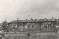 """Unikátní snímek na jeden z baráků bývalého německého ženského tábora, který Jan Irving po válce odkoupil pro potřeby znovuobnoveného skautského oddílu, jehož byl jako kluk členem a nyní už jej i sám vedl, aby pokračoval v tradici. Tyto objekty se nacházely na poměrně rozlehlé louce hned naproti jejich stavení. Dnes jsou zde ovšem dvě bytovky a několik rodinných domů, jejichž stavby """"pohřbily"""" i podzemní protiletecký bunkr, do něhož se dalo bez problémů vstoupit ještě v 90. letech."""