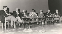 """Jedna z prvních veřejných besed v tehdejším Paláci kultury na pražské Pankráci (dnes Kongresové centrum). Besedy probíhaly měsíc co měsíc zhruba rok a půl a témata se střídala. Snímek je z neděle 16. 9. 1990 a tentokrát byl večer věnován našim """"bombarďákům"""". Sedící zleva jsou: Arnošt Polák (RTG z Janovy posádky, od roku 1948 žil v Anglii), s mikrofonem Vladimír Nedvěd (jeden z velitelů 311. československé bombardovací perutě 1943-1944, po emigraci v roce 1948 žil v Austrálii), Alois Martinovský (mechanik 311. sq.), moderátor Zdeněk Tulis (ten se pravidelně střídal s Tomášem Slámou), Vladimír Slánský (pilot + RTG 311. sq.), Jan Irving a Alois Konopický (zbrojíř 311. sq.). Jelikož ne všichni letci měli k dispozici uniformy, až do poloviny roku 1991 se účastnili veřejných a slavnostních akcí ve stejnokrojích typu """"blejzr"""", což je tmavě modré sako se světle šedými kalhotami."""