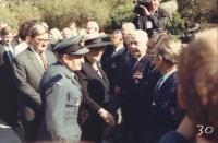 """Opět Olšanské hřbitovy – sekce RAF v roce 1992 při oficiální návštěvě premiérky Margaret Thatcherové, kterou v dobové uniformě RAF za naše letce doprovází obětavý Lojzík Konopický a premiérka se po pozdravu s plk. Irvingem právě chystá podat ruku jeho vedle stojícímu kamarádovi Arnoštu Polákovi. Ten prý následně Janovi pošeptal: """"Já se na to vykašlu. Přes padesát let žiju v Anglii, Margaret mám téměř za zadkem a na to, abych si s ní podal ruku, jsem musel přijet do Prahy!"""" Že se pak oba následně rozesmáli, není asi třeba dodávat."""