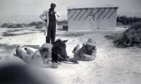 """Jan (vlevo) s oblíbeným oslíčkem v poloze """"lehni""""; ze snímku je patrný nevěřícný pohled jeho arabského pána"""