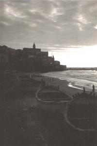 Západ slunce nad pláží v Jaffě s dominantou starého křesťanského chrámu a pevnosti na skále