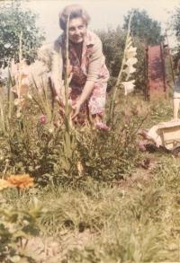 """Úherce v dobách Ivetina nejkrásnějšího dětství, kdy se navíc táta snažil postupně budovat a opravovat náš dům a hlavně dodělávat dvůr a domek pod ním. Mamka milovala své mečíky na zahradě. Za ní je železná klouzačka, kterou táta spolu s obrovskou houpačkou a další menší atrakcí nechal vyrobit už pro své dvě prvorozené děti. Pravda je, že díky tomu na naší zahradě """"vyrostly"""" tři generace dětí (dnes už důchodců), neboť tehdy žádné hřiště v obci nebylo a všichni se scházeli u nás, a to až do doby, než jsem vyrostla i já. Ještě ve pětadvaceti letech jsem se na oné velké houpačce houpala, než mamka rázně rozhodla, že to musí pryč, protože už se vše rozpadá a je to o zabití."""