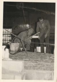 Zadělávání poslední cihly při opravě pece; na fotografii šamotář z Teplotechny (vlevo) a ředitel sklárny Miloslav Dvořák (vpravo), druhá polovina 70. let