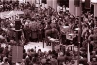 Srocení kolem pultíku moderátorů na náměstí v Havlíčkově Brodě při generální stávce 27. 11. 1989, Tomáš Holenda u pultíku vpravo (poskytlo Muzeum Vysočiny Havlíčkův Brod)