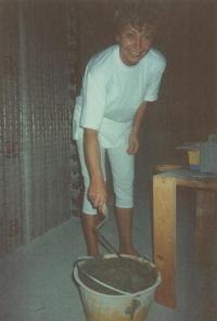 Magda připravuje maltu na omítání, dům u Milána 1991