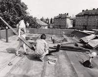 Instalace kinetické plastiky olomouckého architekta a výtvarníka Jiřího Žlebka (dřepící) na střeše kulturního střediska v Rýmařově, jedna z prvních výstav sdružení KAV, 1989