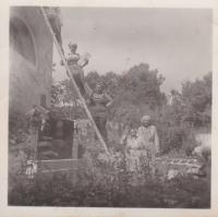 Oprava kostela Nanebevzetí Panny Marie ve Zhoři. Emilie Trpáková u žebříku s uvázaným šátkem kolem hlavy