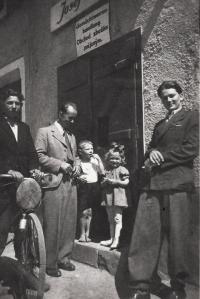 Vpravo strýc Jan Urban před obchodem se smíšeným zbožím (název obchodu uveden  česky a německy)
