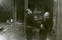 Matka s četníkem vynášejí zboží při požáru rodinného obchodu v lednu 1939