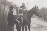 Ivan Martin Jirous se musel ze Staré Říše jezdit každý den hlásit na služebnu do Telče vzdáleného 11 km, aby nemusel chodit pěšky, jezdil na koni. V popředí fotografie maminka pamětnice, Karla Florianová s dcerou.