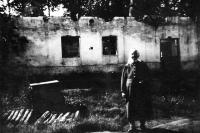 Babička Jiřího Bárty před poničeným statkem číslo 24 v Porubě / 1945