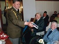 Otec Jaroslava Moravce Josef (vlevo na vozíku, vedle manželka) přebírá vojenské vyznamenání u příležitosti oslavy stých narozenin