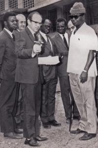 Vladimír Zikmund v Kongu při misi proti černým neštovicím. V ruce drží očkovací pistoli a ukazuje ji konžskému ministru zdravotnictví (muž v huňaté čepici)