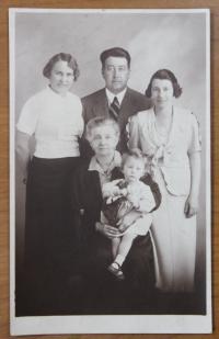 v náručí babičky, stojící strýc s manželkou a její matka