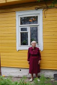 Józefa Goroszewicz at the front of her house.