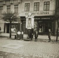 Dobová fotografie domu rodiny Strauchů s kožešnictvím a pumpou, v popředí otec a jeho dva synové