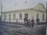 Vlevo rodina Holcova, Josef Holec nejvyšší z dětí úplně vpravo, v pozadí čeledín