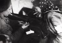 Britský voják Leslie zapaluje Ditě cigaretu, Bergen-Belsen 1945