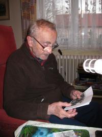 Pamětník při rozhovoru ukazuje fotografie