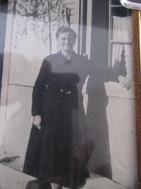 Mother  in front of family house