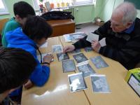 Zdeněk Mandrholec ukazuje žákům letecké snímky jáchymovských pracovních táborů, 2016
