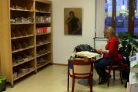 Vernisáž výstavy v Husově knihovně v Modřanech, u stolu sedí Hošnova neteř, na stěně visí obraz Cikánka, který Hošna namaloval v době studií; Modřany, 23. 3. 2015