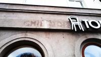 Zbytky nápisu velkoobchodu EMIL BOHÁČEK, Karlovo náměstí 3
