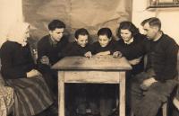 Rodina Kovalčukova za 2. sv. války při poslechu rozhlasu, babička pamětníka první zleva