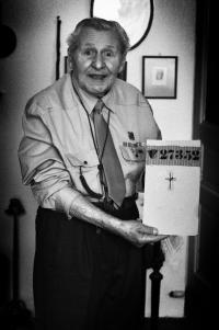 František Wretzl dnes. V rukou drží své vězeňské číslo z koncetračního tábora. 2011.