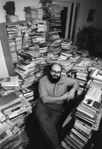 Kornel in their apartment surrounded with books