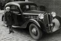 Little Augustin next to a car