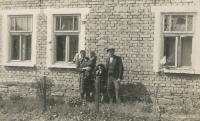 rodiče pamětníka s jeho sourozenci před jeho rodným domem v Tršicích, na kterém je vidět poškození od granátů