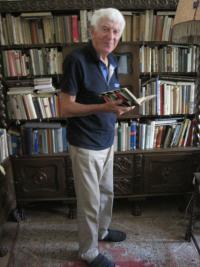 Ladislav Lašek at his library and with a book by the most beloved author - Karel Čapek